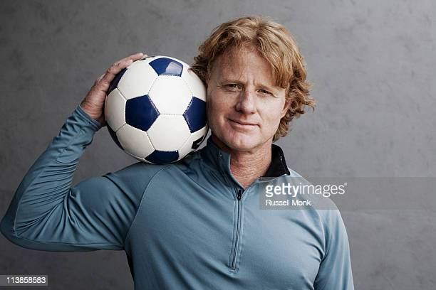 Redhead holding a soccer ball on his shoulder