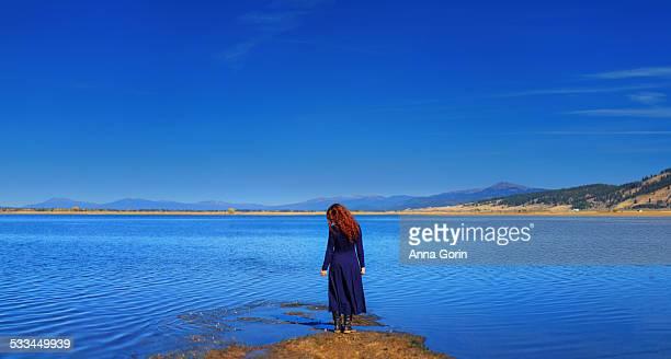 Redhead in blue dress alone at lake edge