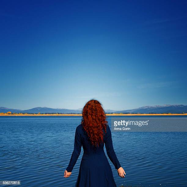 Redhead in blue dress faces rippled lake