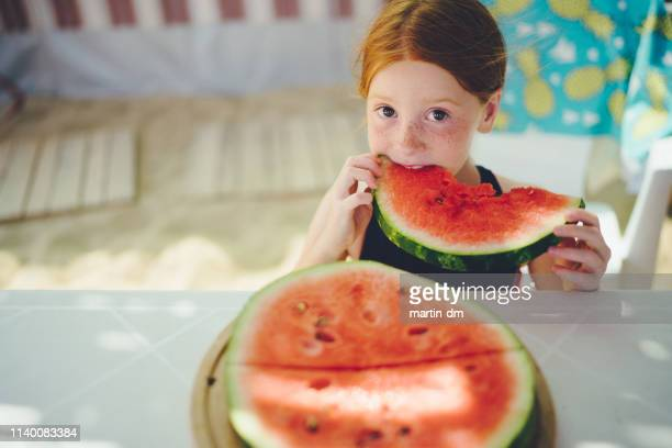 redhead kid with freckles eating watermelon on beach holiday,portrait - hot dirty girl stock photos and pictures