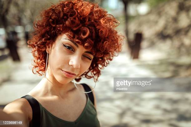 redhead latin woman taking selfie outdoor - dyed red hair stock pictures, royalty-free photos & images