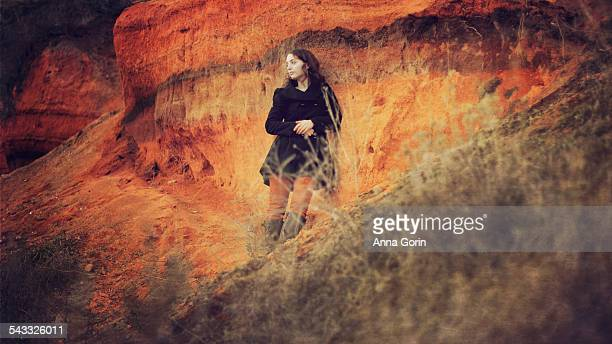 redhead leans on sandstone rock formation, texture - pコート ストックフォトと画像