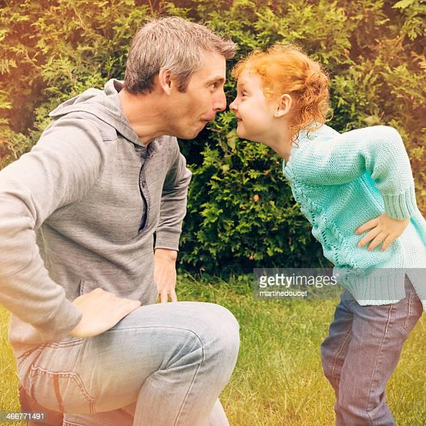 Pelirrojo niña y Padre que s'enfrenta, en la zona suburbana de jardín.