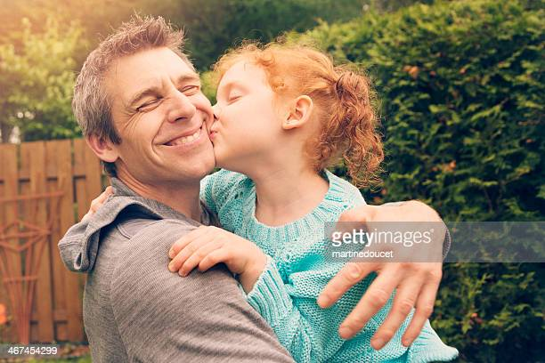 Redhead little girl kissing and hugging father outdoors.