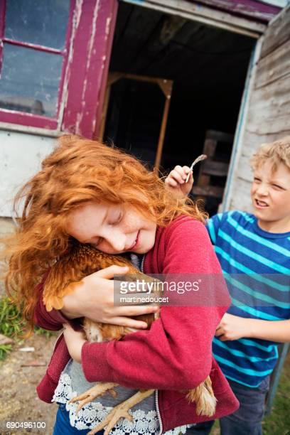 """ruiva menina ternamente segurando e abraçando uma galinha. - """"martine doucet"""" or martinedoucet - fotografias e filmes do acervo"""