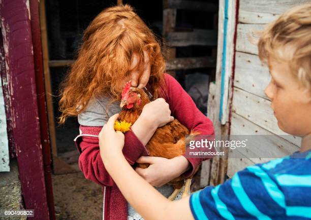 Redhead little girl tenderly kissing and holding a hen.