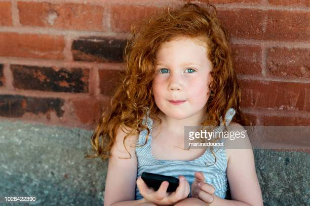 Redhead little girl with mobile phone outdoors on a brick wall.