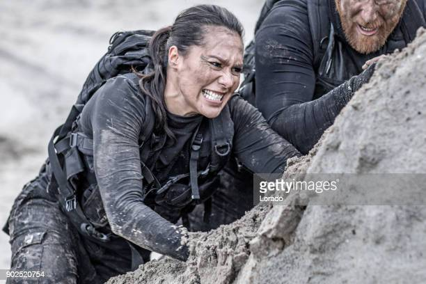 redhead male and brunette female military members training hard and helping each other on a sand hill run - struggle stock pictures, royalty-free photos & images