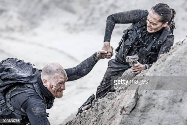 redhead male and brunette female military members training hard and helping each other on a sand hill run - military exercise stock pictures, royalty-free photos & images