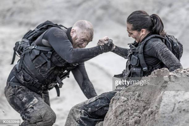 redhead male and brunette female military members training hard and helping each other on a sand hill run - doing a favor stock pictures, royalty-free photos & images