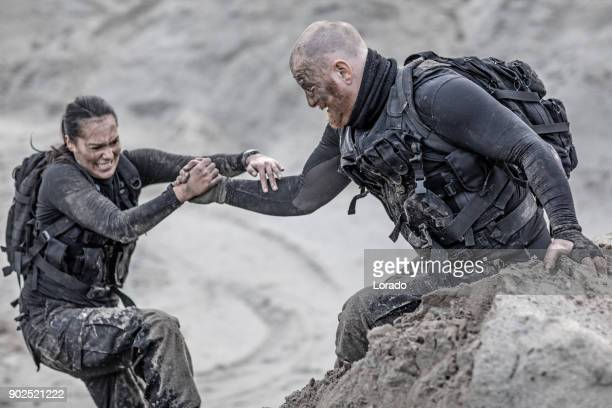 redhead male and brunette female military members training hard and helping each other on a sand hill run - sports team event stock photos and pictures
