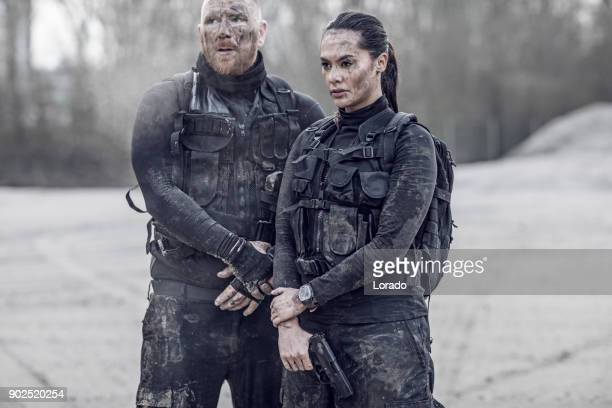 redhead male and brunette female military swat security anti terror duo standing during operations in abandoned construction site - swat team stock photos and pictures