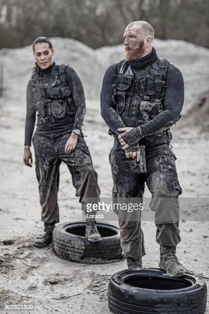 redhead male and brunette female military swat security anti terror duo standing during operations in abandoned construction site - task force stock pictures, royalty-free photos & images