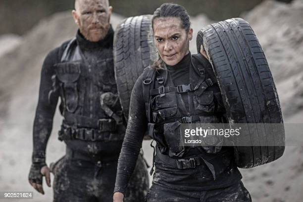 redhead male and brunette female military swat security anti terror duo during operations in abandoned construction site - special forces stock pictures, royalty-free photos & images