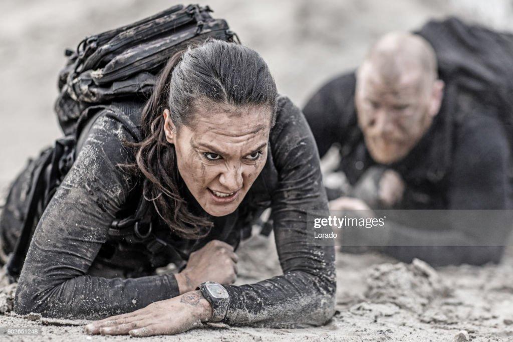 Rothaarige Männer und Brünette weibliche Militär swat Sicherheit anti-Terror-Duo zusammen während der Operationen in schlammigen Sand krabbeln : Stock-Foto