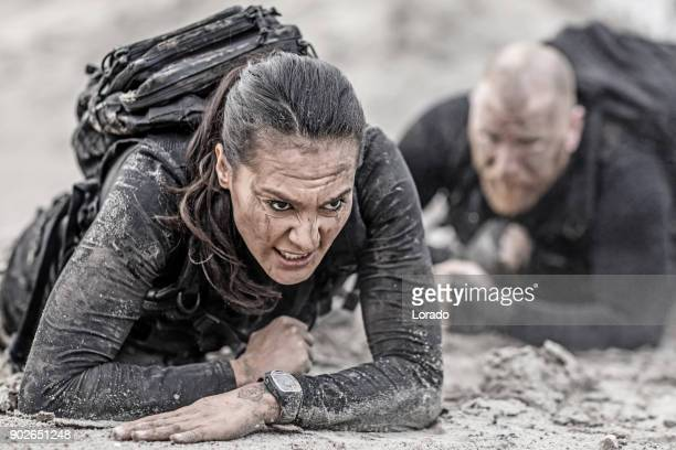 redhead male and brunette female military swat security anti terror duo crawling  together during operations in muddy sand - army soldier stock photos and pictures