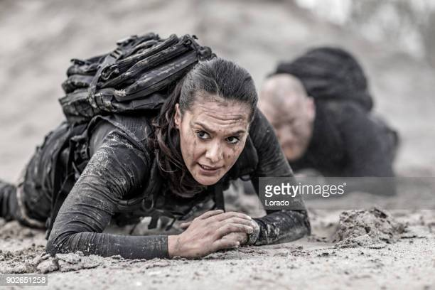 redhead male and brunette female military swat security anti terror duo crawling  together during operations in muddy sand - military training stock pictures, royalty-free photos & images