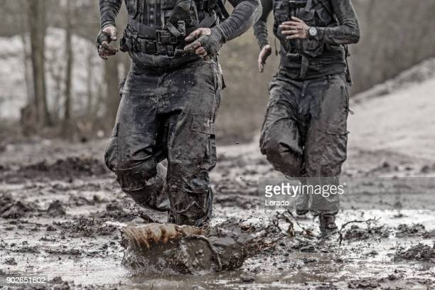 redhead male and brunette female military swat security anti terror duo during operations in outdoor muddy setting - military training stock pictures, royalty-free photos & images