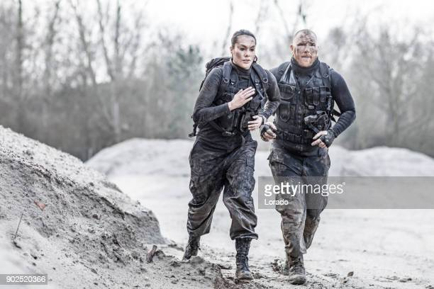 Redhead male drill instructor running with beautiful brunette female soldier outdoors in the mud