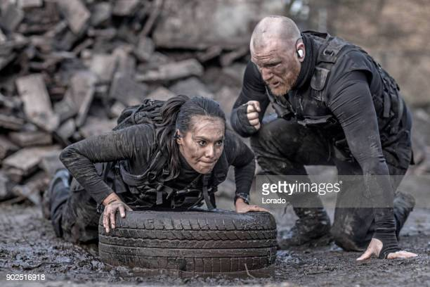 Redhead male drill instructor training beautiful brunette female soldier using a tire outdoors in the mud