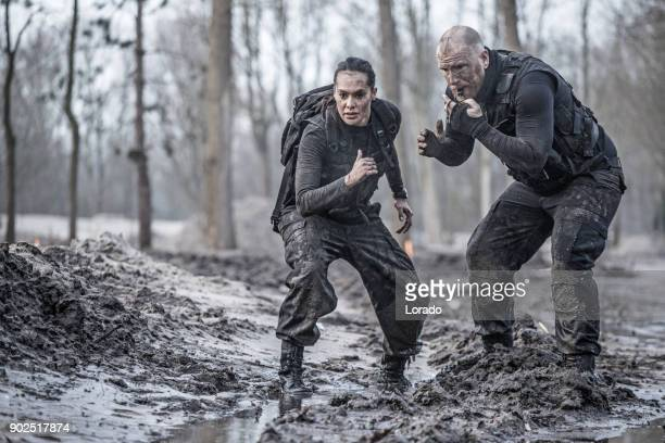 Redhead male drill instructor training beautiful brunette female soldier doing sprints outdoors in the mud