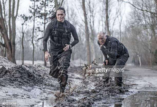 Rothaarige männliche Drill Instruktor Ausbildung schöne Brünette Soldatin Sprints im Freien in den Schlamm zu tun