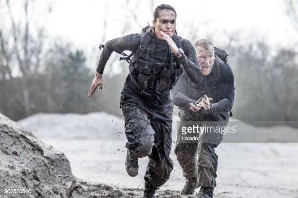 redhead male drill instructor training beautiful brunette female soldier doing sprints outdoors in the mud - personale militare foto e immagini stock
