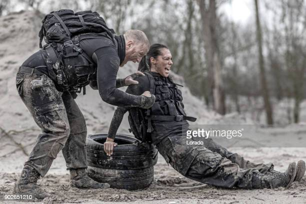 Redhead male drill instructor training beautiful brunette female soldier using tires outdoors in the mud