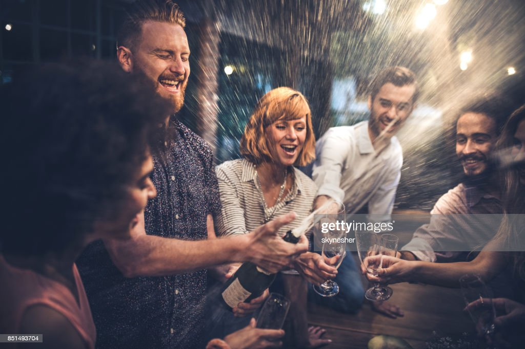 Redhead man opening a champagne on a party with his friends. : Stock Photo