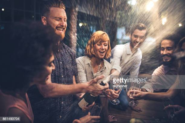 Redhead man opening a champagne on a party with his friends.