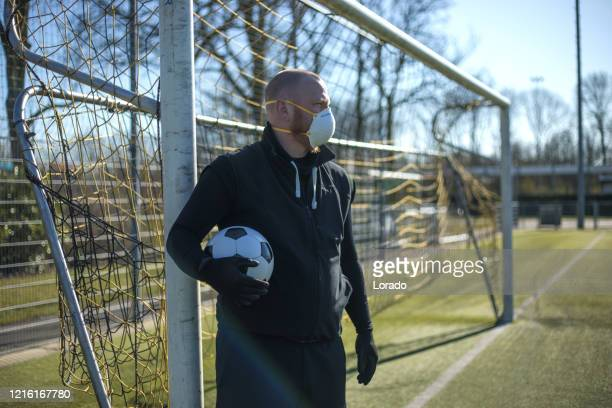 redhead man wearing a face mask and holding a soccer ball at a football complex - amateur stock pictures, royalty-free photos & images
