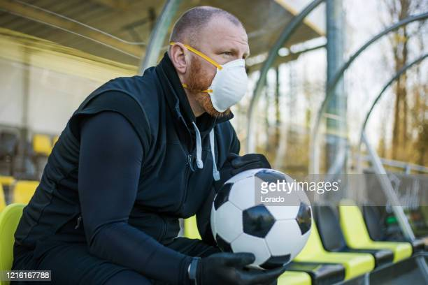 redhead man wearing a face mask and holding a soccer ball at a football complex - football face mask stock pictures, royalty-free photos & images