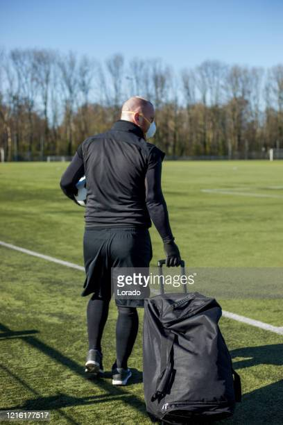 redhead man wearing a face mask and holding a soccer ball at a football complex - international team soccer stock pictures, royalty-free photos & images