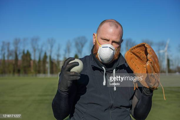 redhead man wearing a face mask and holding baseball equipment at a sports field - international team soccer stock pictures, royalty-free photos & images