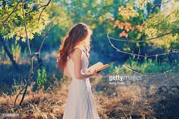 Redhead reads book outdoors, sunlit under tree, wearing sleeveless white dress