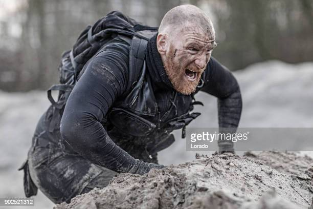 Redhead shaved male military member training hard on a sand hill run