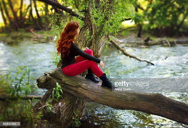 Redhead sits on fallen log, looking out at river