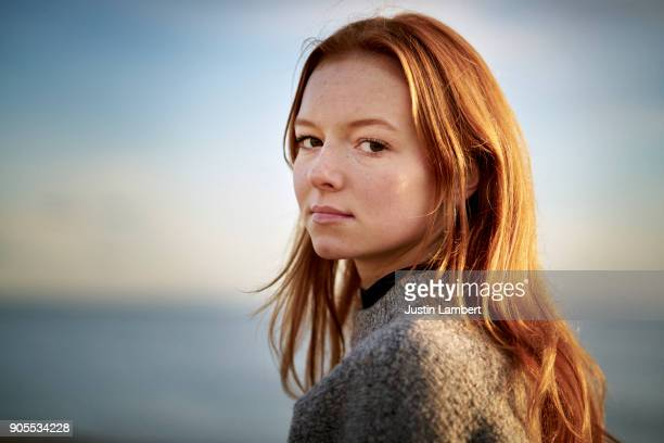 redhead teenager looking to camera in winter sunlight on beach - serious stock pictures, royalty-free photos & images