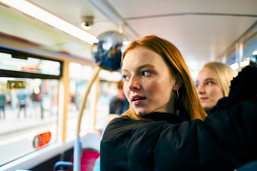 Redhead teenager travelling with a group of friends on the bus, holding on to the handrail and looking out of the window at something or someone or thinking or contemplating - gettyimageskorea
