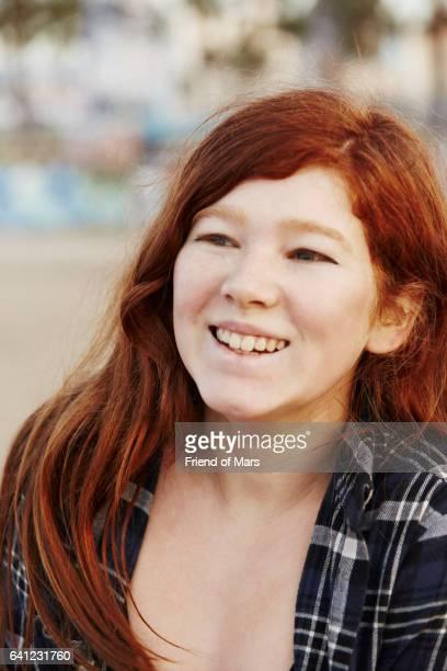 Redhead teenager wearing plaid shirt smiling.