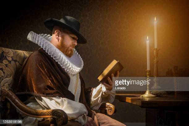 redhead traditional dutch man reading a book by candlelight - duke stock pictures, royalty-free photos & images