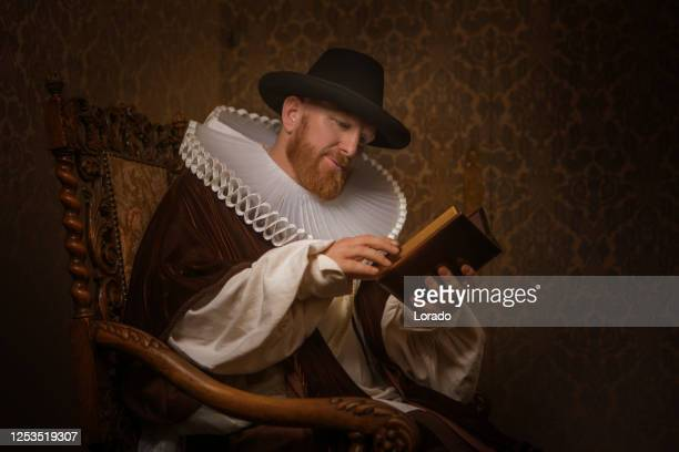 redhead traditional dutch man reading a book - duke stock pictures, royalty-free photos & images