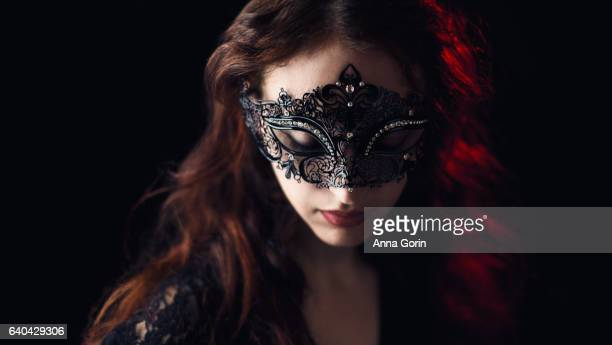 Redhead wearing black Victorian masquerade mask looks down, black studio backdrop with low lighting