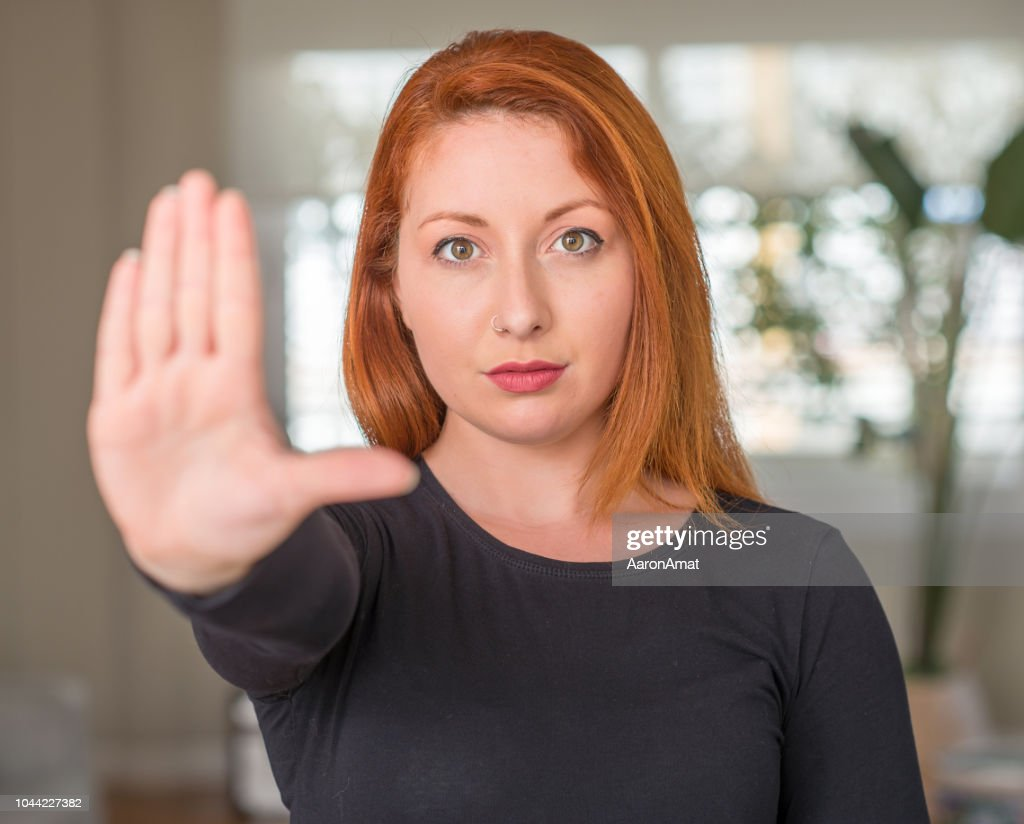 Redhead woman at home with open hand doing stop sign with serious and confident expression, defense gesture : Stock Photo