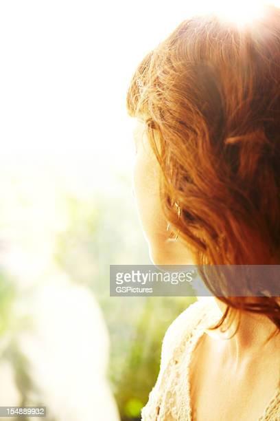 Rotes Haar-Frau von hinten angestrahltes von Sonne mit Blick in die Natur