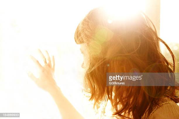 Redhead woman backlit by sun with hand on glass window