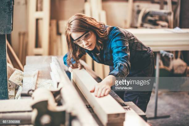 redhead woman cutting a plank - carving craft product imagens e fotografias de stock