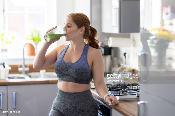 redhead woman drinking healthy milkshake after working out at home - drink stock pictures, royalty-free photos & images