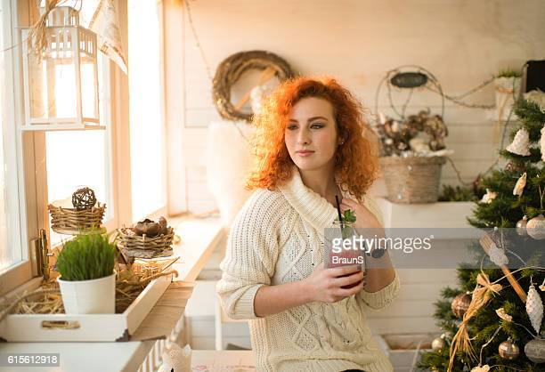 Redhead woman enjoying in fruit smoothie on New Year's day.