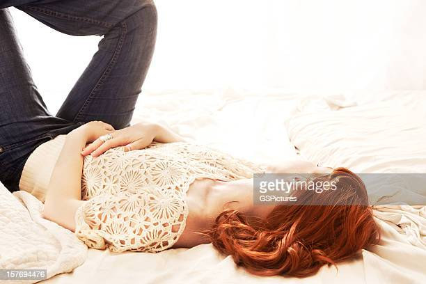 Redhead woman lying in bed backlit by a window